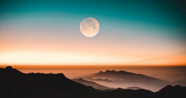 Vollmond über Bergen in farbigem Himmel